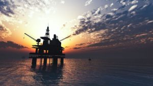 An oil rig at sea with the sun setting